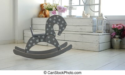 Swaying wooden horse on the floor