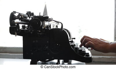 Man printing text with the typewriter, closeup view