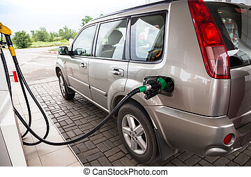 Refilling the car - Green fuel nozzle in pouring to SUV
