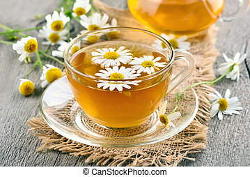 Chamomile tea - Herbal chamomile tea in glass cup on wooden...