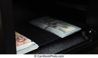 Hand puts money in the safe - Hand puts and closed money in...