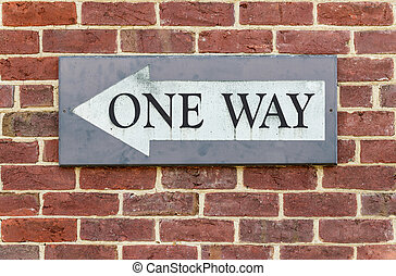 One way sign on a brick wall