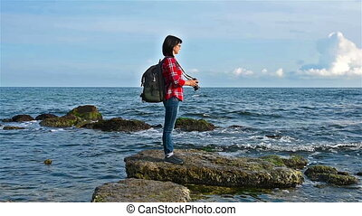 hipster girl photographing sea - hipster girl with backpack...