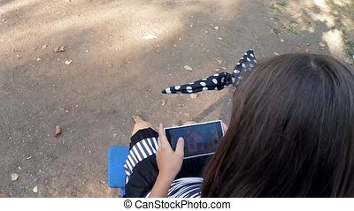 SLOW MOTION. Girl playing in the park on your smartphone -...