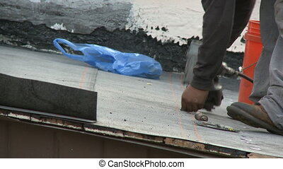 Roofer installing tin caps on flat roof