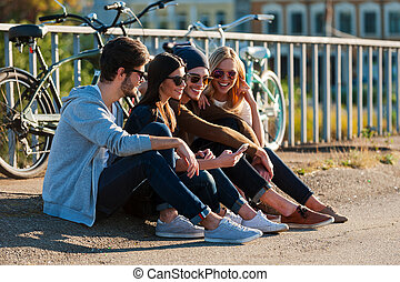 Relaxing after day riding. Group of young smiling people bonding to each other and looking at smart phone while sitting outdoors together with bicycles in the background
