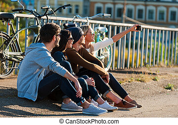 Time for selfie. Group of young smiling people bonding to...