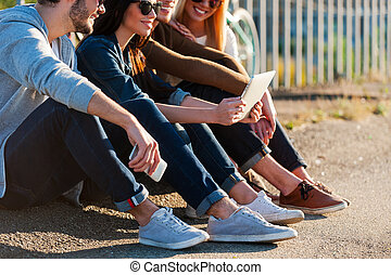 Enjoying wireless technologies. Close-up of group of young smiling people bonding to each other and looking at digital tablet while sitting outdoors together