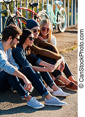 Young and carefree. Close-up of group of young smiling people bonding to each other and looking at digital tablet while sitting outdoors together with bicycles in the background