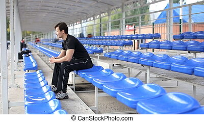 athlete runner resting sitting at the university stadium -...