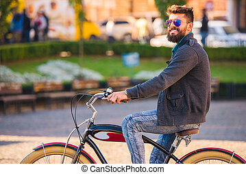 Man with bicycle - City bike. A young man with a beard, walk...