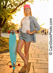 Overjoyed girl holding skateboard - Nice time Pleasant...