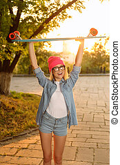 Overjoyed girl holding skateboard - Full of happiness...
