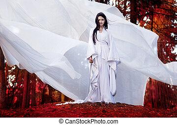 Asian woman in white kimono holding samurai sword