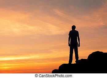 Silhouette of a man at the sunset on the mountain