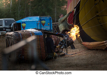 filling balloon with hot air from gas burner - Process of...