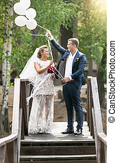 Happy bride and groom holding white balloons at windy day -...