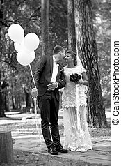 groom holding balloons kissing beautiful bride at park -...