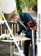 young groom signing wedding contract during ceremony at park...