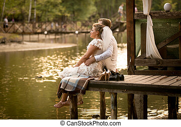 just married couple sitting on pier at river and looking at sunset