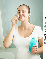Portrait of woman removing makeup with lotion and cotton pad...