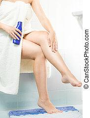 Closeup of woman applying moisturizing creme after shaving...