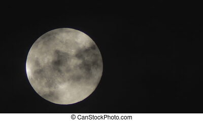 Full moon in the night sky over the trees and clouds - Full...