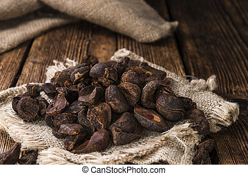 Cola Nuts (dried) as close-up shot on rustic wooden...
