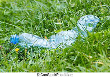 Plastic bottle of mineral water on grass in park, littering...