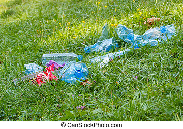 Heap of rubbish on grass in park, littering of environment -...