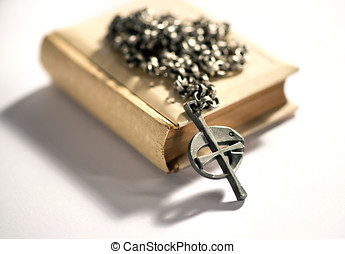 Fish cross rosary lying on a Bible