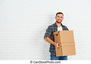 moving to a new apartment happy man with cardboard boxes -...