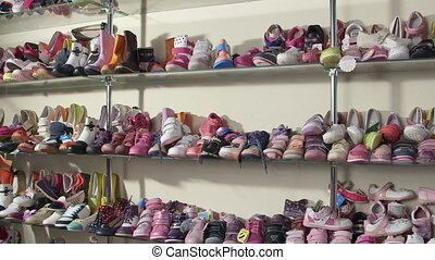 footwear in the shoe store - Rows of shelves piled high with...