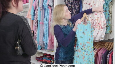 client in clothing department - Sales assistant showing...