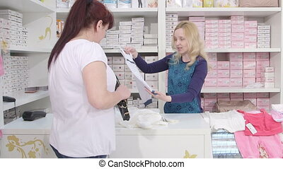 female client in baby shop - Sales assistant showing new...