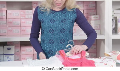 client in baby shop - Sales assistant showing new infant...