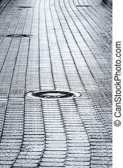 sewer manhole cover on wet cobblestone street - metal sewer...