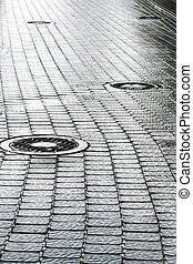 sewer manhole on wet cobblestone street - steel sewer...