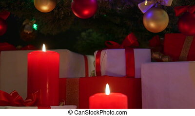 boxes under Christmas tree - Burning candles and gifts boxes...