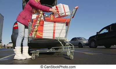 Girl with shopping cart full of gift boxes and Christmas...
