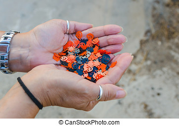 Halloween confetti - Two female hands holding a bunch of...