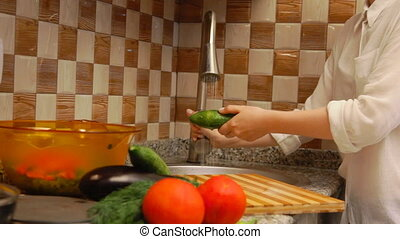 Woman preparing cucumbers - Young woman making a salad with...