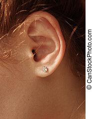 Female ear with diamond earrings