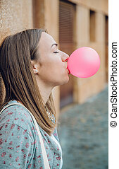 Young teenage girl blowing pink bubble gum - Closeup of...