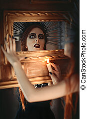 Strange goth girl holding candle in hand and looking into mirror