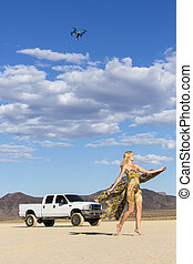 Model Posing with Car in Desert - A model poses with a car...