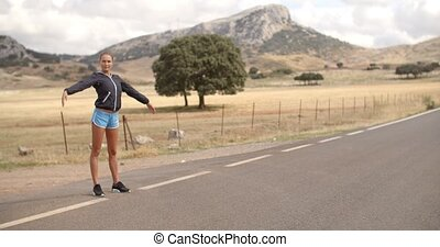 Sporty Woman Standing Alone on the Road Ready to Run with...