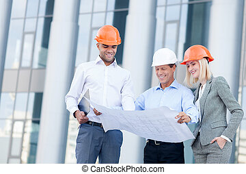Cheerful three builders are planning new project -...