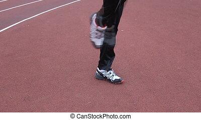 Runner warming up legs flexing - Runner legs flexing
