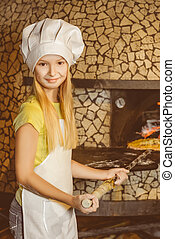 Girl Chef put the pizza in hot oven at restaurant